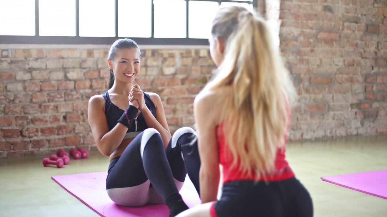 Zwei Frauen beim Trainieren auf einer Yogamatter
